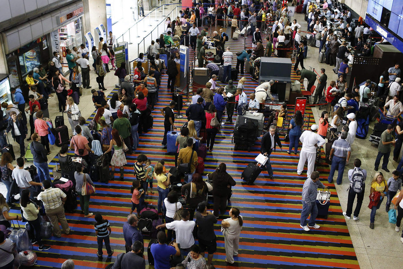 Passengers line up for the security checkpoint at Simon Bolivar airport in La Guaira, outside Caracas October 15, 2013. President Nicolas Maduro's government plans to use fingerprint machines at airports to try to root out no-shows who buy tickets to scam travel-related currency controls without even flying, in the latest symptom of Venezuela's economic chaos. REUTERS/Carlos Garcia Rawlins (VENEZUELA - Tags: POLITICS)